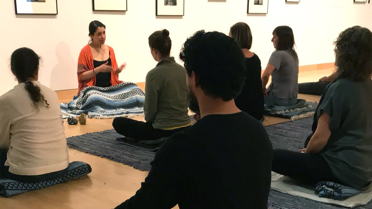 A group of people sit cross-legged on yoga mats while an instructor speaks.