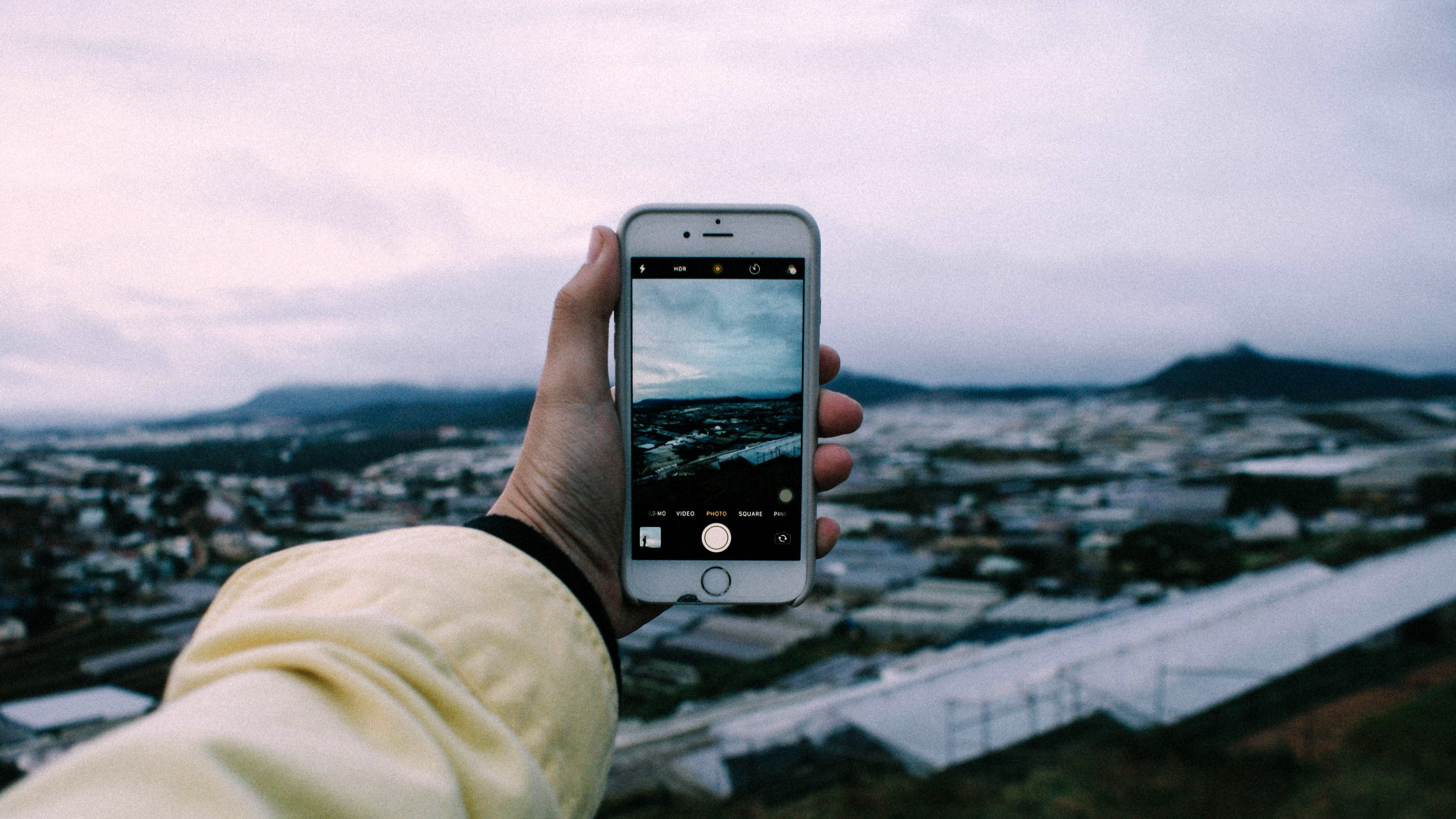 A person holds up a smartphone to take a picture of an urban landscape on an overcast day.