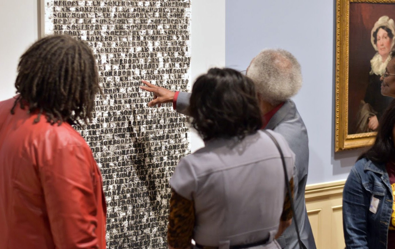 Three people examine and point at a painting by Glenn Ligon.