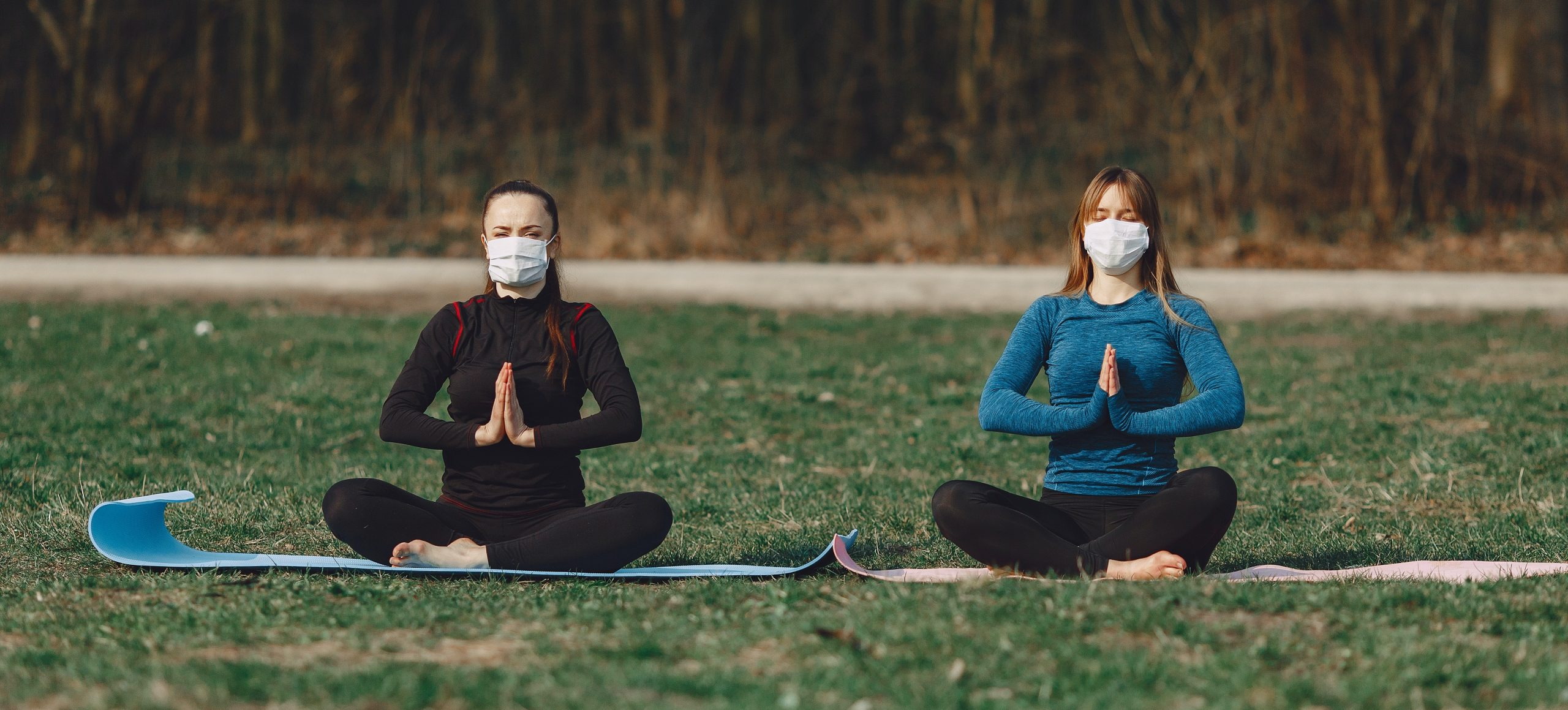 Two women do yoga outside. They are six feet apart and wear face masks.