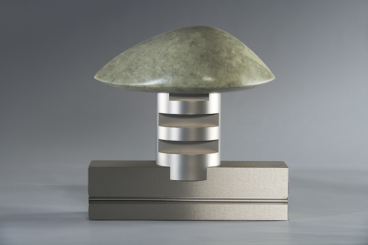 A metallic sculpture with a stone disk on top of a cylinder.