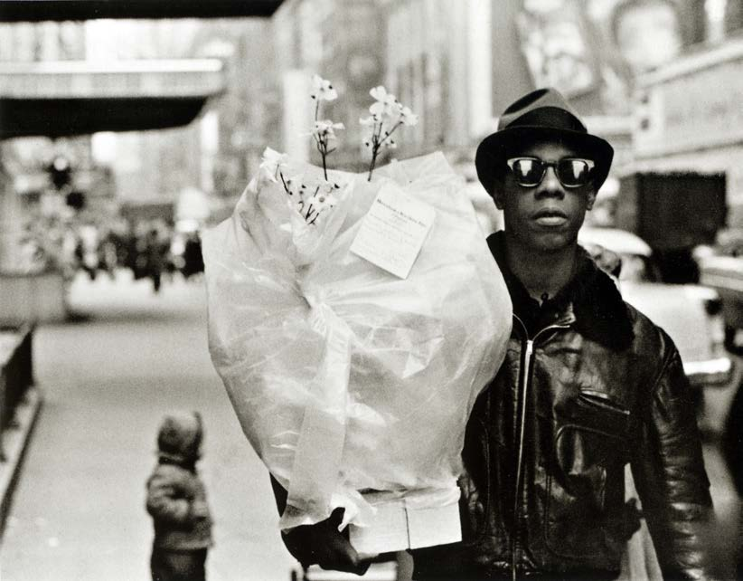 A Black man in street fashion holds a bouquet of flowers wrapped in plastic.