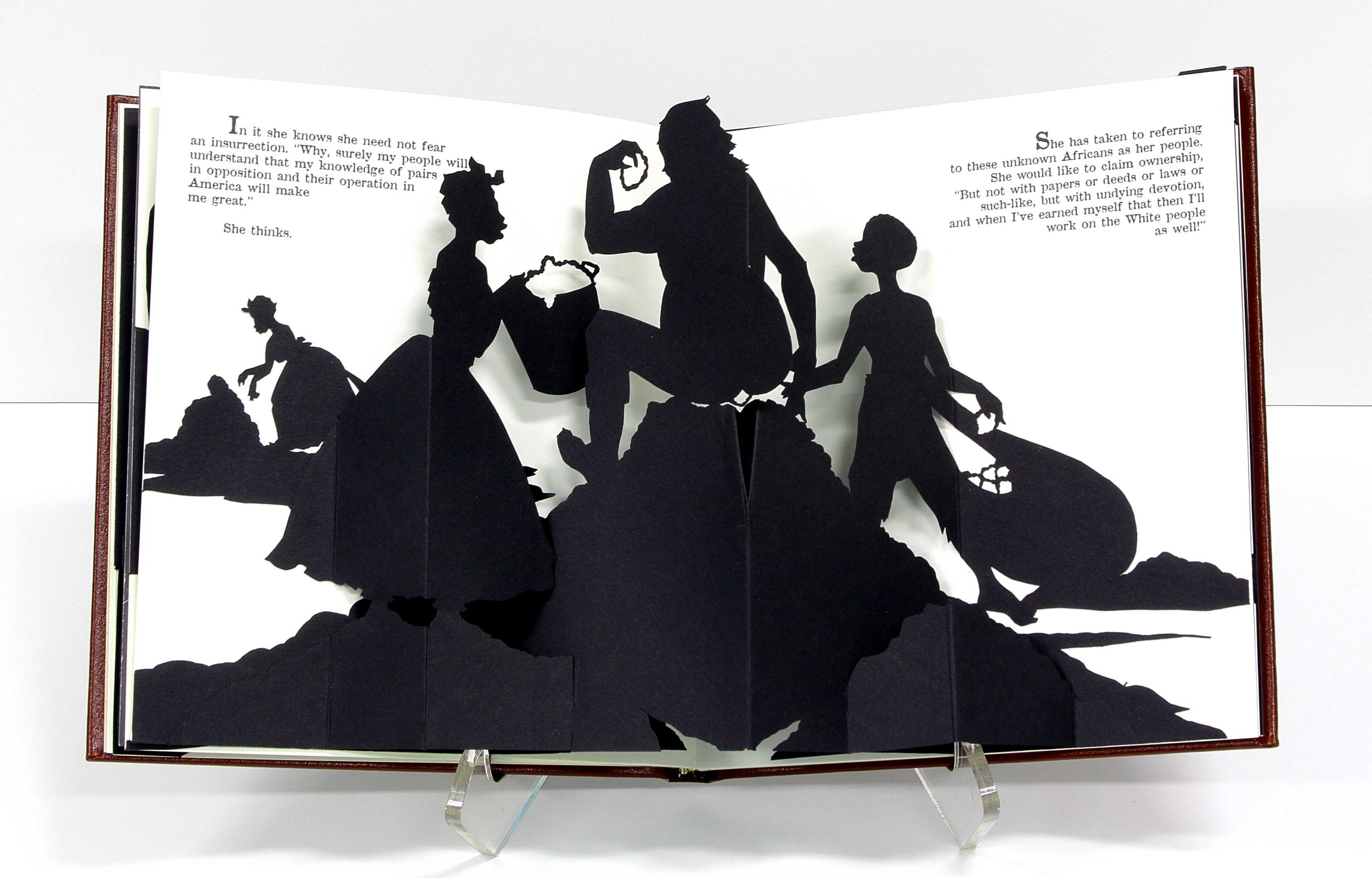 A book with 3D cardstock pop outs of people and mounds on the ground. A person sits on top of a mound with one person offering a bucket and another dragging a sack approaching.