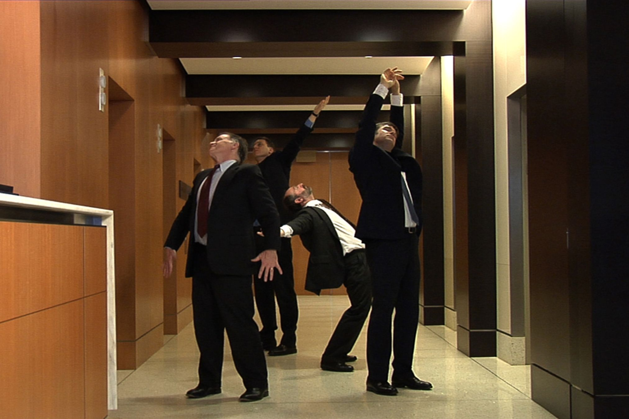 Men in suits stretch in a hall with wood panels.