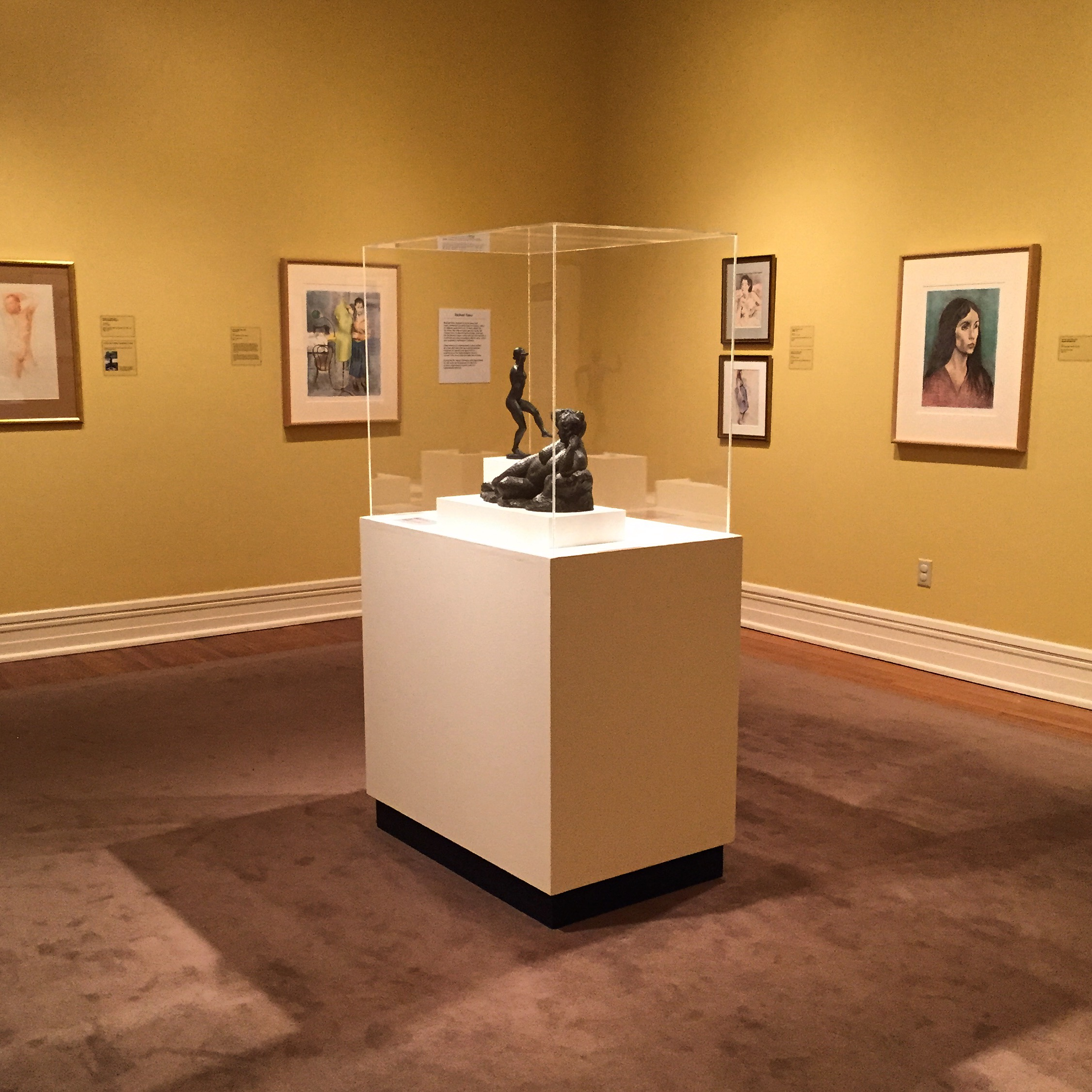 A gallery room with paintings on the wall and a glass case with a small sculpture.