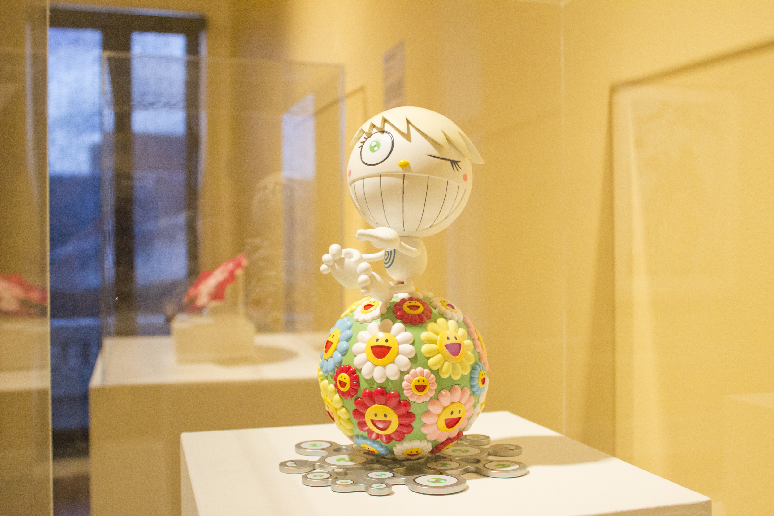 A case of a figure that is smiling and winking made from two balls. The lower section of the figure is covered in smiling flowers.