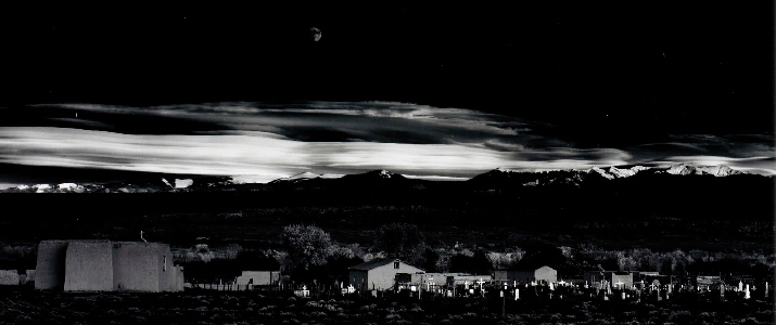A landscape of homes and a mountain at night.