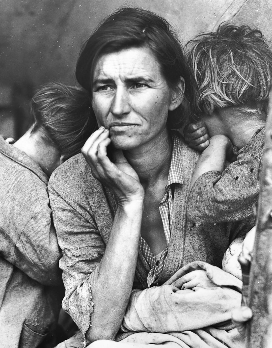 Black and white image of a woman looking into the distance with two children clung to her.