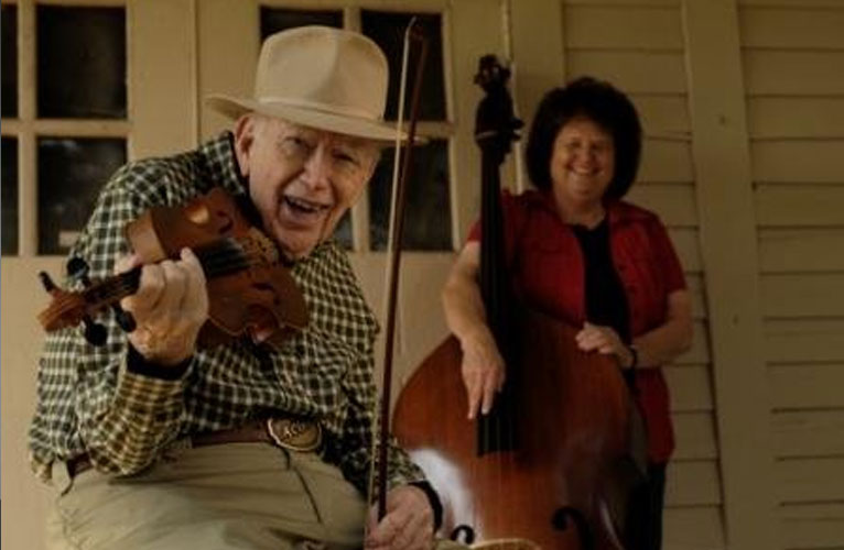 Two people on the front porch of their home holding instruments.