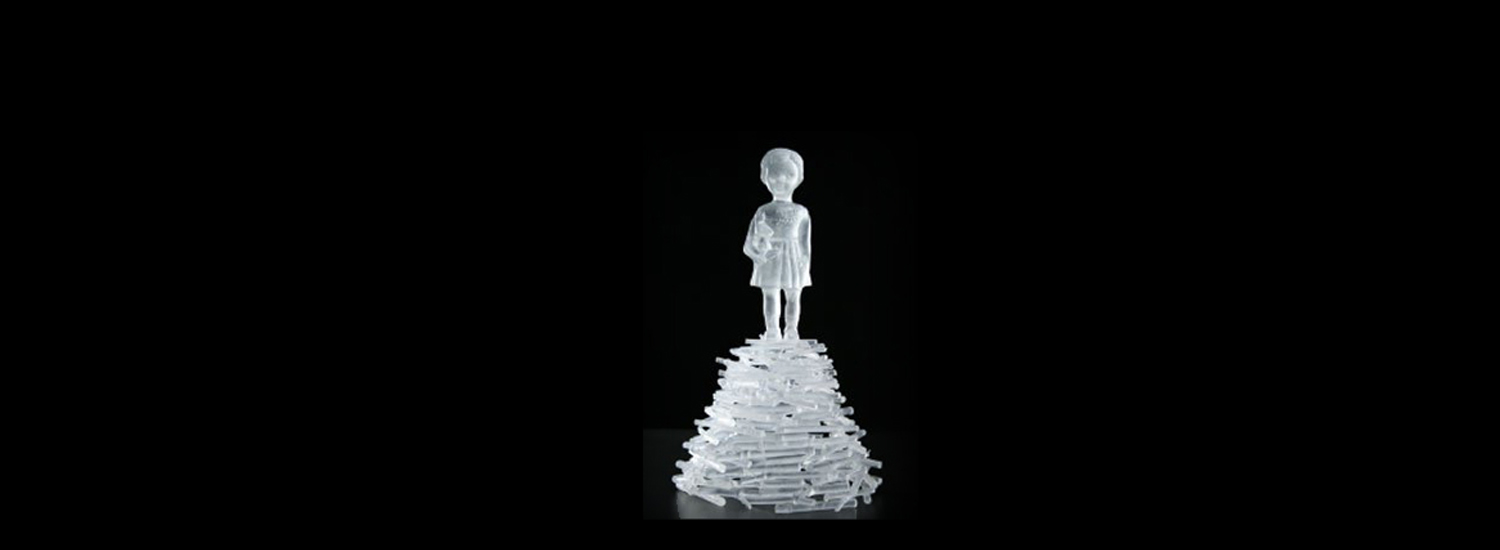 A glass sculpture of a child on top of a pile of bricks.