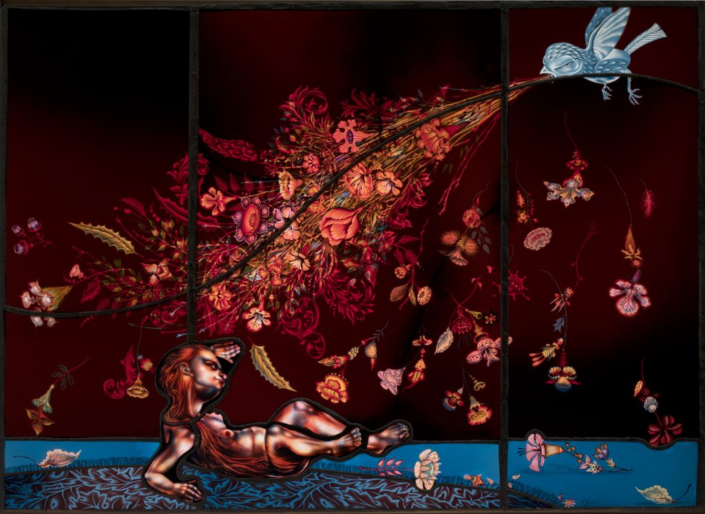 Stained glass of a bird spewing pink hues of flowers out of its mouth onto a person crouching on the blue ground below it.