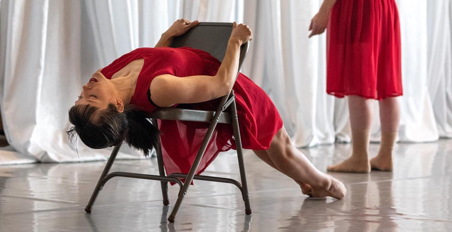 Two dancers in red dresses. One dancer is laying on her back stretched on a chair with her feet pointed.